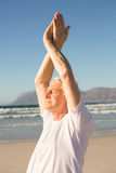 Senior man with eyes closed exercising at beach Stock Photography
