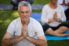 Senior man with eyes closed meditating in prayer position Stock Photography