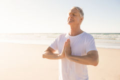 Senior man with eyes closed in prayer position at beach. On sunny day stock photo