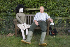 Senior man with eyes closed by scarecrow on bench stock images
