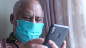 Senior man with face mask using smart phone at home
