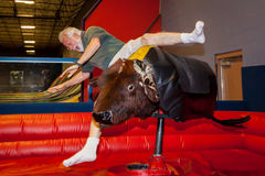 Senior Man Falls Off Mechanical Bull. A senior man falls off of a mechanical bull. He has an open mouth and hands out to catch himself royalty free stock photo