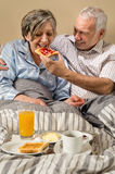 Senior man feeding breakfast to woman Royalty Free Stock Images