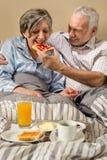 Senior man feeding breakfast to woman Royalty Free Stock Images