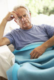 Senior Man Feeling Unwell Resting Under Blanket Stock Photo