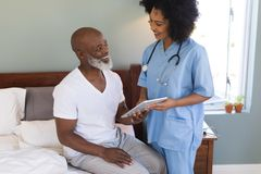 Senior man and female doctor using digital tablet at home stock image
