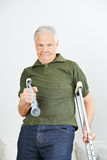 Senior man fighting with crutches Stock Images
