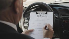 Senior man fills a resume sitting in a car. Recruitment. stock video