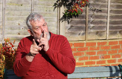 Senior man. Finger to mouth indicating, be quiet. A senior man holding his finger to his mouth and looking straight at the camera and pointing finger. The man Stock Photo