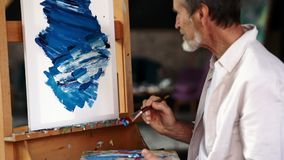 Senior man finishing his acrylic abstract picture. Artist with brush and palette sitting in front of an easel stock video footage