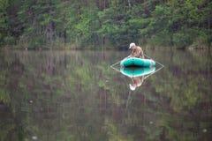 Senior man fishing from a boat Royalty Free Stock Image
