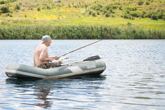 Senior man fishing from a dinghy in a lake Royalty Free Stock Images
