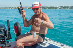 Senior man fishing. A senior man enjoy fishing on a boat in the mediterranean sea in Italy Stock Images