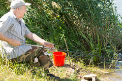 Senior man fishing on a freshwater lake Stock Images