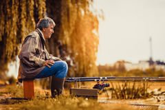 Senior man fishing on a freshwater lake sitting patiently Stock Images