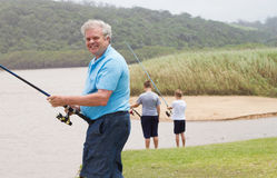 Senior man fishing with grandsons Royalty Free Stock Images