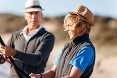 Senior man fishing with his grandson. Senior men fishing with his teenage grandson at seaside stock image