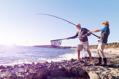Senior man fishing with his grandson Royalty Free Stock Image