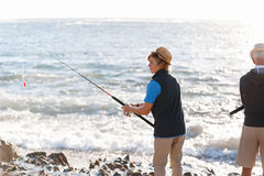 Senior man fishing with his grandson Stock Photography