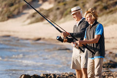 Senior man fishing with his grandson Royalty Free Stock Images