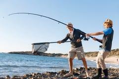 Senior man fishing with his grandson Royalty Free Stock Photo