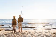 Senior man fishing with his grandson Royalty Free Stock Photos