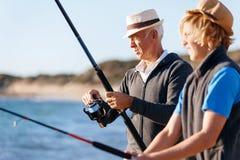 Senior man fishing with his grandson Stock Image