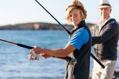 Senior man fishing with his grandson Stock Photo