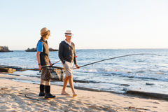 Senior man fishing with his grandson. Senior men fishing with his teenage grandson at seaside royalty free stock image