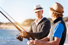 Senior man fishing with his grandson. Senior men fishing with his teenage grandson at seaside royalty free stock photography