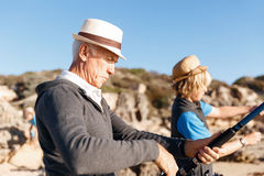 Senior man fishing with his grandson. Senior men fishing with his teenage grandson at seaside stock photo