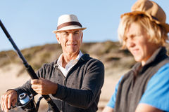 Senior man fishing with his grandson. Senior men fishing with his teenage grandson at seaside stock photography