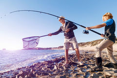 Senior man fishing with his grandson. Senior men fishing with his teenage grandson at seaside royalty free stock photos