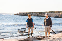 Senior man fishing with his grandson. Senior men fishing with his teenage grandson at seaside royalty free stock images
