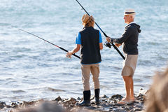 Senior man fishing with his grandson. Senior men fishing with his teenage grandson at seaside stock photos
