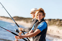 Senior man fishing with his grandson. Senior men fishing with his teenage grandson at seaside royalty free stock photo