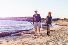 Senior man fishing with his grandson. Senior men fishing with his teenage grandson at seaside royalty free stock image