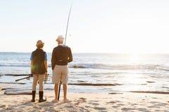 Senior man fishing with his grandson. Senior men fishing with his teenage grandson at seaside stock photography