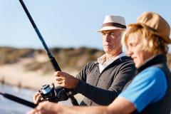 Senior man fishing with his grandson. Senior men fishing with his teenage grandson at seaside royalty free stock photo
