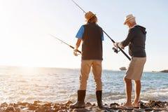 Senior man fishing with his grandson. Senior men fishing with his teenage grandson at seaside royalty free stock images