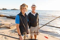 Senior man fishing with his grandson. Senior men fishing with his teenage grandson at seaside stock photos
