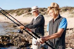 Senior man fishing with his grandson. Senior men fishing with his teenage grandson at seaside stock photo