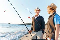 Senior man fishing with his grandson. Senior men fishing with his teenage grandson at seaside royalty free stock photography