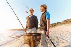 Senior man fishing with his grandson. Senior men fishing with his teenage grandson at seaside royalty free stock photos