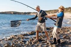 Senior man fishing with his grandson. Senior men fishing with his teenage grandson at seaside stock image