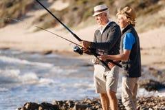 Senior man fishing with his grandson. Senior men fishing with his teenage grandson at seaside stock images
