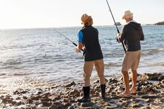Senior man fishing with his grandson royalty free stock photo