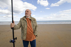 Senior man with fishing rod on beach, hand in pocket, low angle view Royalty Free Stock Photo