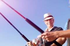Senior man fishing at sea side stock images