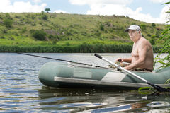 Senior man fishing from a rubber dinghy Royalty Free Stock Image